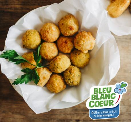 Small baked food balls in a bowl with white paper